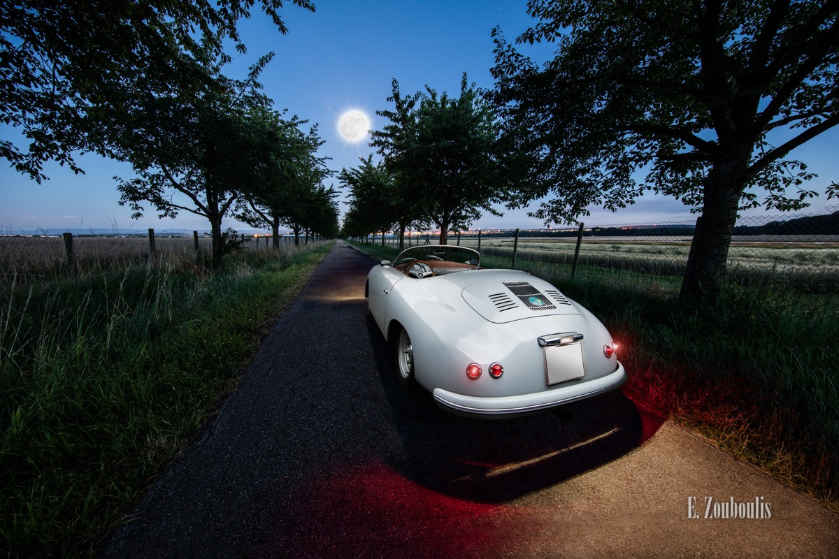 Ein Porsche 356 Speedster. Foto vom Heck im dunkeln, mit Blick auf den Vollmond entlang der Baumallee und den Feldern