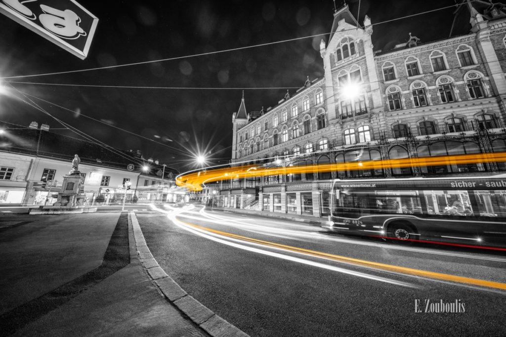 Schwarzweiß-Aufnahme am Margaretenplatz in Wien mit gelbem Lichtschweif, der den Verkehr kennzeichnet.