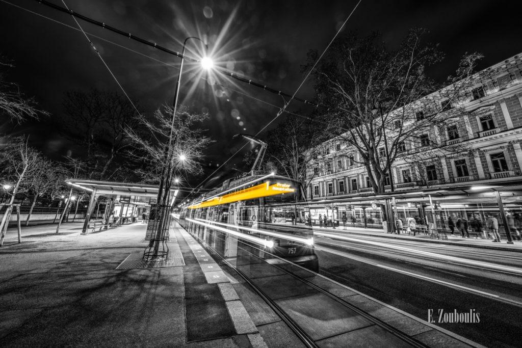 """Schwarzweiß-Fotografie am Burgring in Wien mit einfahrender Straßenbahnen in gelber Aufschrift """"1 Prater Hauptallee""""."""