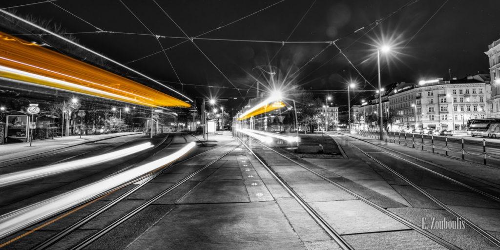 Schwarzweiß-Fotografie am Karslplatz in Wien mit vorbeifahrenden Straßenbahnen in gelb.