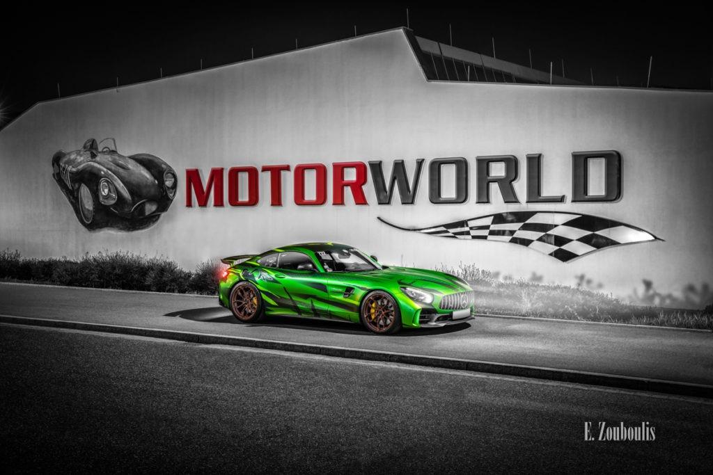 Schwarzweiss-Aufnahme eines Sievers Performance AMG GTR Green Tiger in grün. Im Hintergrund ist das Gebäude der Motorworld mit roter Aufschrift am Flugfeld Böblingen zu sehen