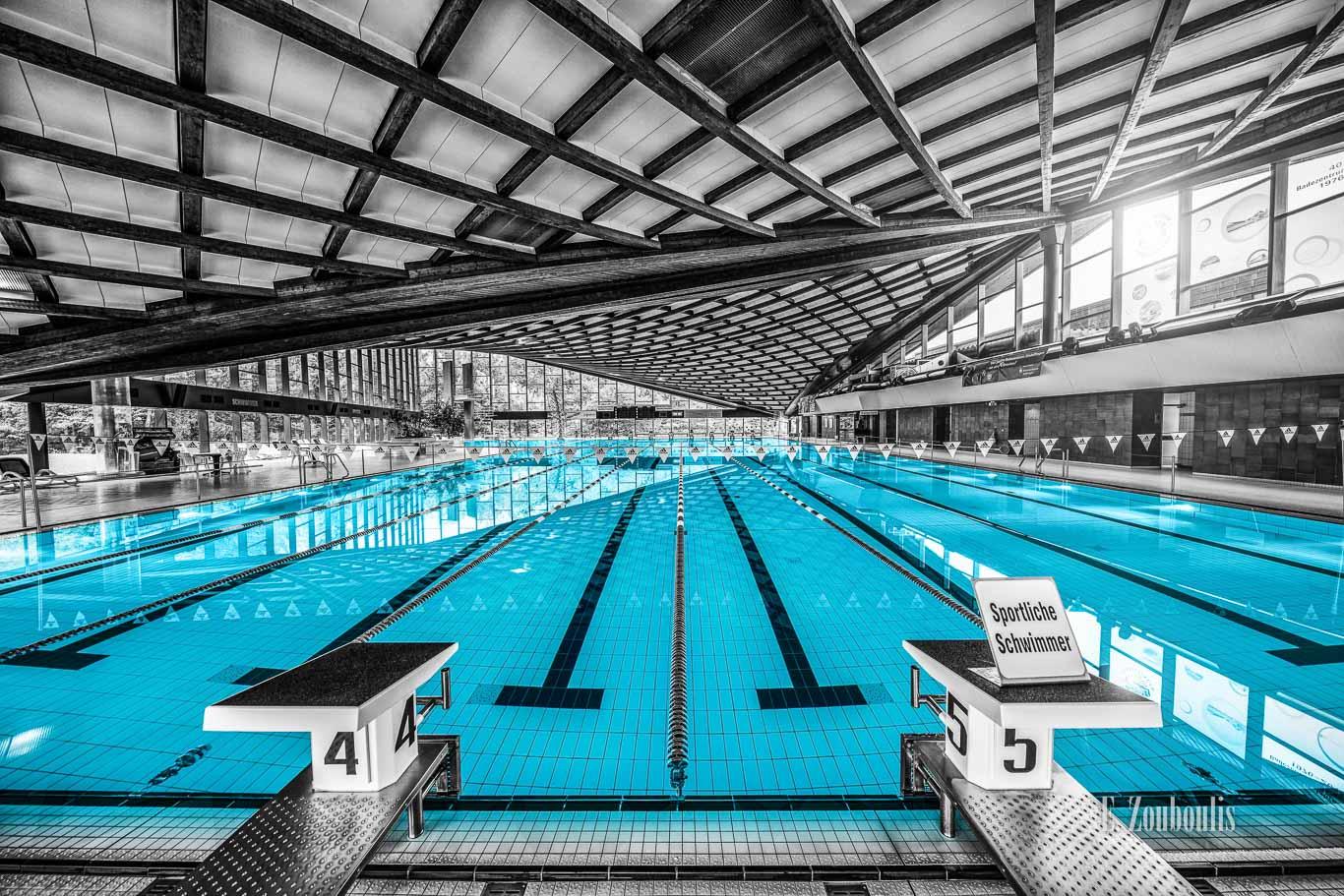 Architekturfotografie - Schwarzweiß Aufnahme im Inneren des Badezentrum Sindelfingen. Das Wasser in den Becken ist in blau zu sehen. Frontal-Ansicht auf das 50m Becken. Im Hintergrund ist der Sprungturm zu sehen