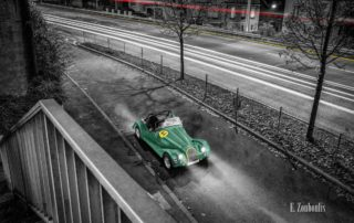 Bild eines Morgan Plus 4 Super Sports an der Weinsteige in Stuttgart. Im Hintergrund ist der vorbeifahrende Verkehr zu sehen