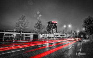 Motorworld Böblingen mit vorbeiziehendem Verkehr bei Nacht