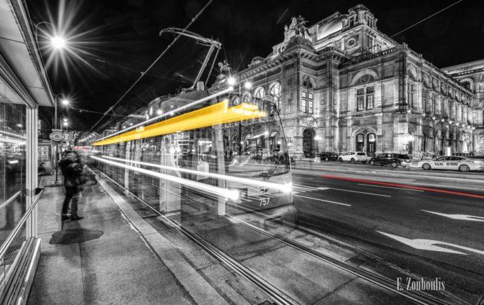 Bild einer Tram vor der Oper in Wien am Opernring. Schwarzweiß mit gelben und roten Light Trails